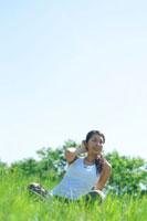 草原の中でヨガをする健康的な20代の女性
