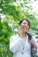 並木道で通勤途中に携帯電話で話をする20代のビジネスウーマン 20027005073| 写真素材・ストックフォト・画像・イラスト素材|アマナイメージズ