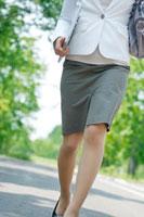 自然の多い公園の並木道を歩く20代のビジネスウーマンの足元