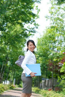 自然の多い公園の並木道で微笑む20代のビジネスウーマン