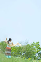 夏の日差しを浴びて草原でストールを持つ20代の女性の後姿