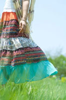 夏の日差しの中で草原に立つ20代の女性の足元