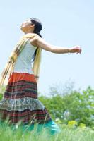 夏の日差しの中で草原に立つ20代の女性の横顔