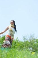 夏の日差しの中で草原を歩く20代の女性