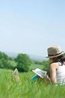 夏の日差しの中で草原に座り本を読む20代の女性の後姿