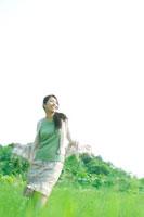 草原を歩く20代の女性