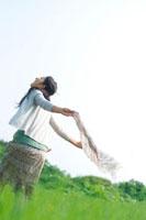草原でストールを風になびかせて歩く20代の女性