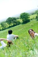 草原でリラックスをする20代の若者たち