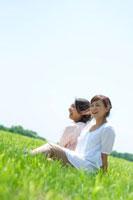 青空と草原に座り微笑む2人の20代の女性
