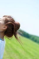 草原で風に髪をなびかせる20代女性の後姿