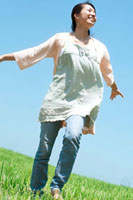 風を感じながら草原を歩く20代の女性