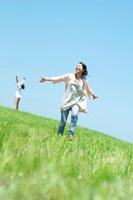 風を感じながら草原を歩く2人の20代の女性