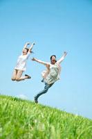 草原でジャンプをする2人の20代の女性