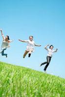 草原でジャンプをする3人の20代の若者たち