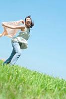草原でカーディガンを風になびかせて歩く20代の女性