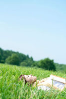 草原で本を持ち目を閉じる20代の女性
