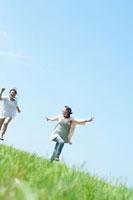 青空と草原を走る2人の20代の女性