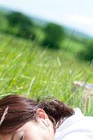 草原に寝転び音楽を聴く20代の女性