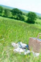 草原の上に置かれた敷物と鞄 20027005171| 写真素材・ストックフォト・画像・イラスト素材|アマナイメージズ