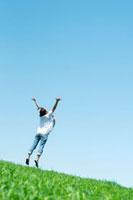 草原で青空に向かってジャンプをする20代の女性