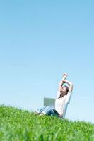 草原でノートパソコンをしながら深呼吸をする20代の女性