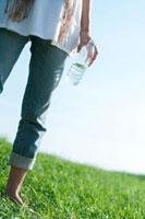 草原でペットボトルの水を持つ20代の女性