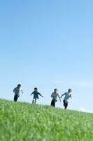 青空と草原を走る4人の20代の若者たち