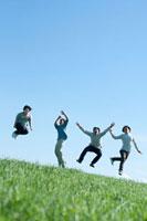 青空と草原でジャンプをする20代の若者たち