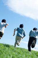 青空と草原を走る3人の若者たちの後姿 20027005212| 写真素材・ストックフォト・画像・イラスト素材|アマナイメージズ