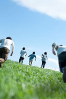 青空と草原を走る5人の若者たちの後姿