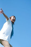 青空と両手を広げてはしゃぐ20代の女性