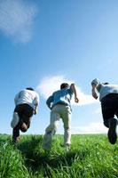 青空と草原を走る3人の20代の若者たちの後姿