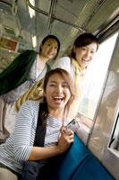 デジカメを持ち旅行を楽しむ3人の20代の女性