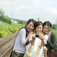 駅のホームでデジカメで写真を撮る3人の20代の女性