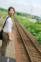 駅のホームで旅行鞄を持ち汽車を持つ20代の女性