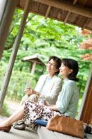 旅館の縁側に座りお茶を飲みながら談笑をする2人のシニア女性