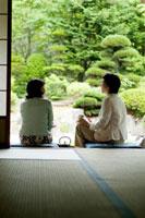 旅館の縁側に座り庭園を眺める2人のシニア女性の後姿