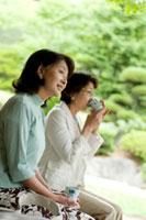 旅館の縁側に座りお茶を飲む2人のシニア女性