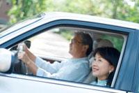 車でドライブを楽しむシニア夫婦