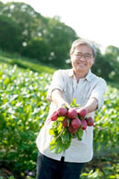 農園で採れたての赤かぶを持つシニア男性