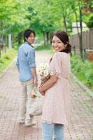 買い物帰りの花束とエコバックを持つ20代のカップル