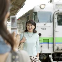 駅のホームで携帯電話で写真を撮る2人のシニア女性