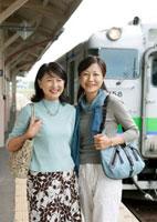 駅のホームで微笑む2人のシニア女性