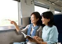 電車で旅行を楽しむ2人のシニア女性 20027005384| 写真素材・ストックフォト・画像・イラスト素材|アマナイメージズ