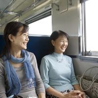 電車で旅行を楽しむ2人のシニア女性