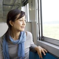 電車で旅行をするシニア女性