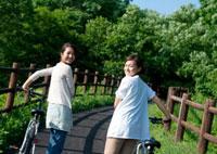 自転車を押しながら振り返る2人の20代女性