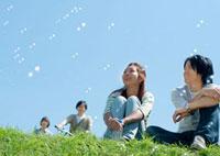 シャボン玉と芝生に座り微笑む20代のカップル 20027005493| 写真素材・ストックフォト・画像・イラスト素材|アマナイメージズ
