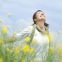 菜の花畑で深呼吸をする20代の女性