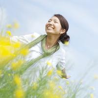 菜の花畑で両手を広げる20代女性
